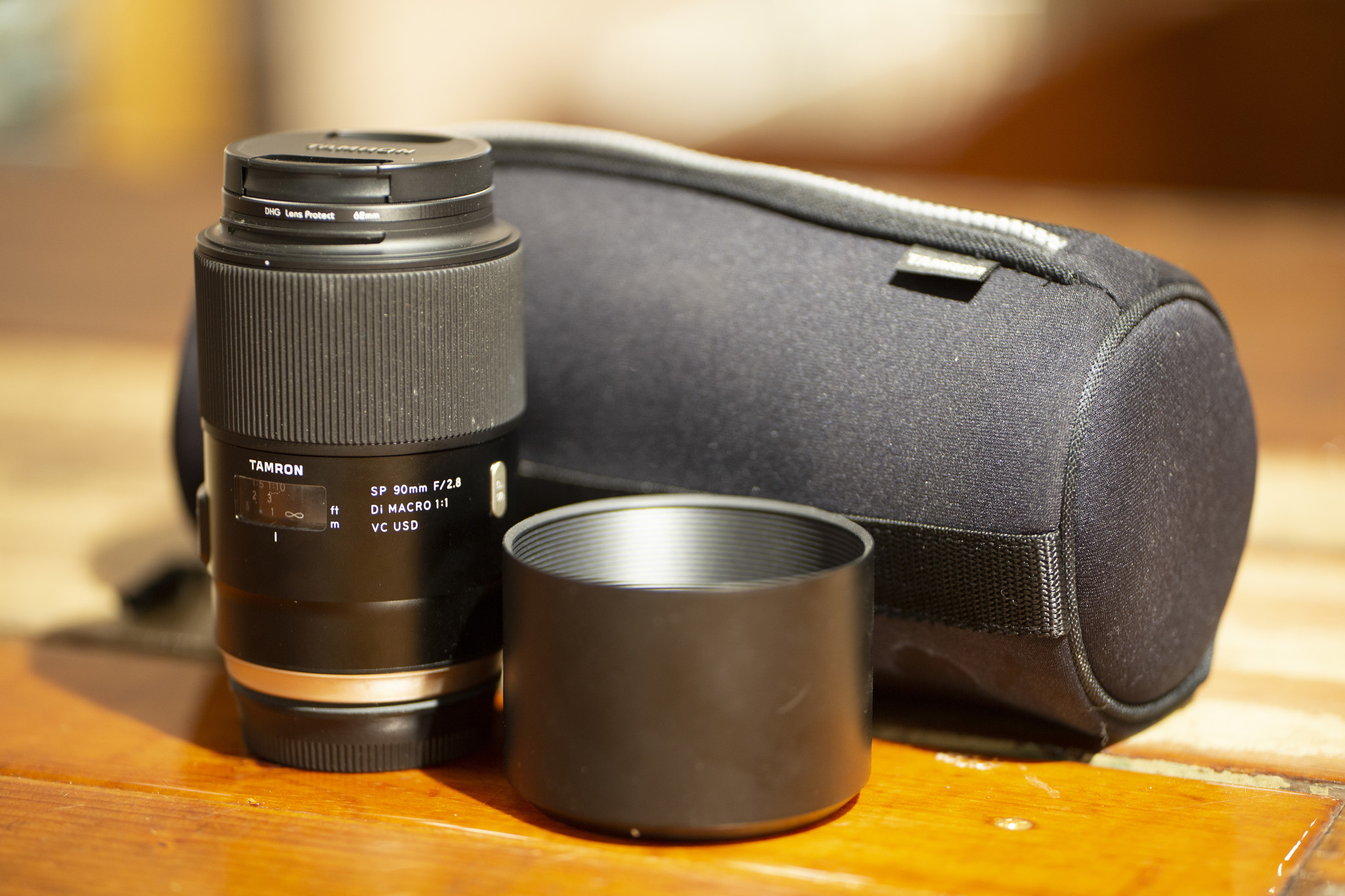 A Tamron lens rental including a Tamron lens and lens case, a DHG filter, and a lens hood.