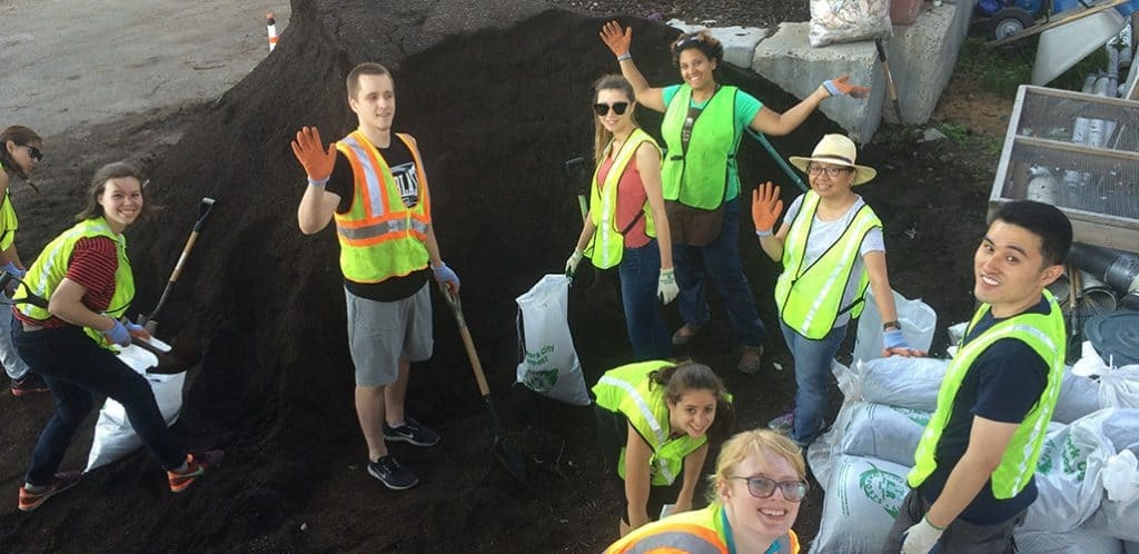 Volunteers wave in front of pile of finished compost