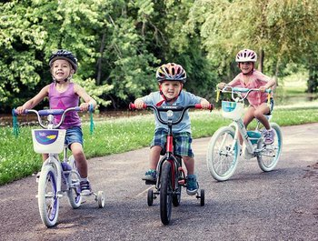 Happy kids ride their bikes to school.