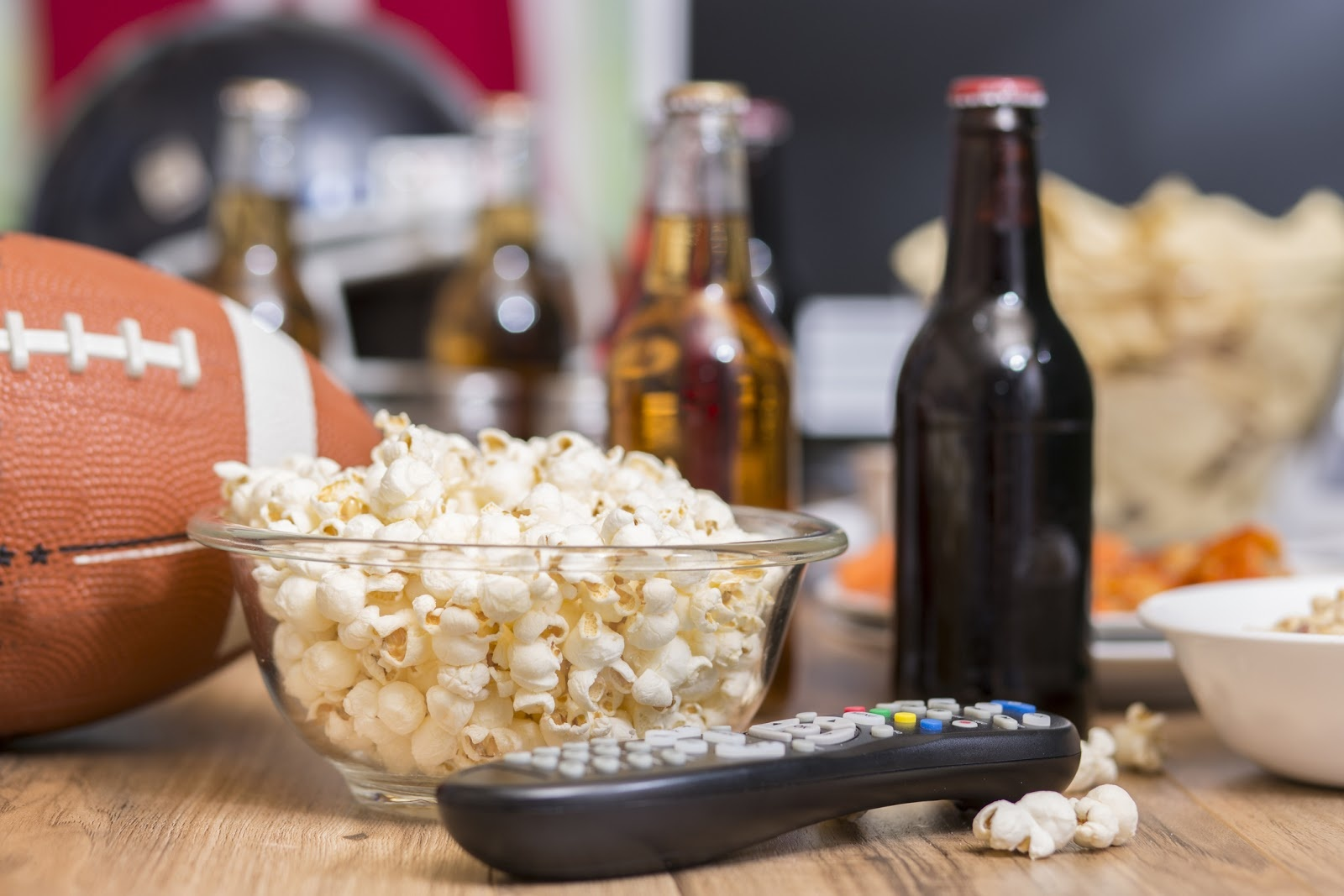 A football watching party set up with a bowl of popcorn, tv remote, football, and beers.