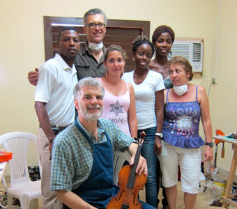 Tom Metzler and David Gage of New York work with violin repair trainees in an impromptu repair shop in Havana, Cuba.
