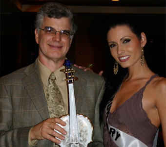 Tom Metzler receives a hand-painted porcelain violin from Adrienn Bende, Miss Hungary, at a charity silent auction at the 2006 'Miss Universe' competition.