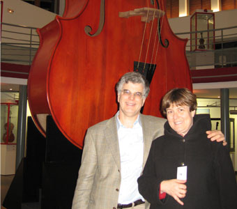 Tom and Barbara stand in front of the world's largest cello, in Mirecourt France.