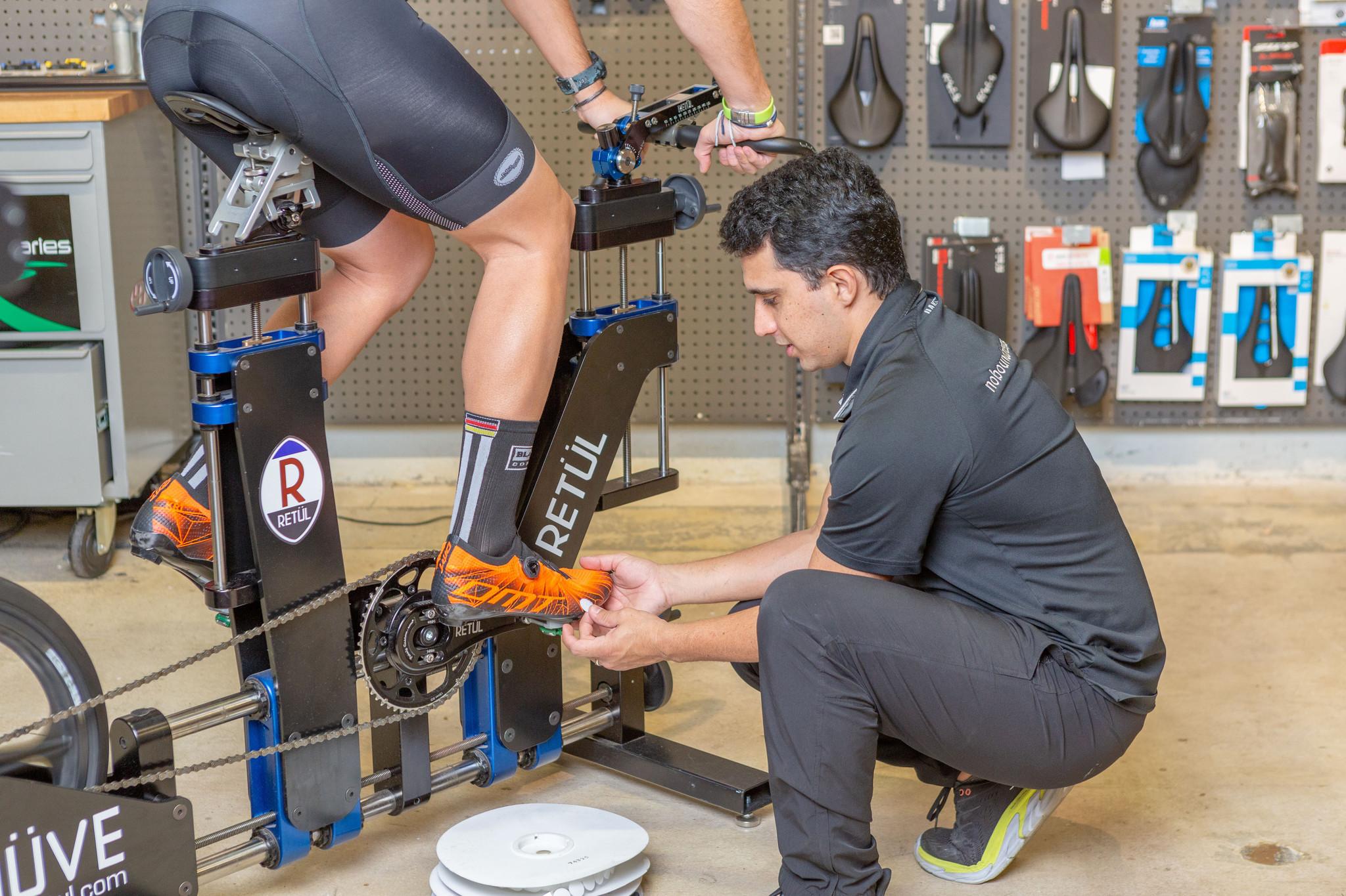 man adjusting cyclist shoes