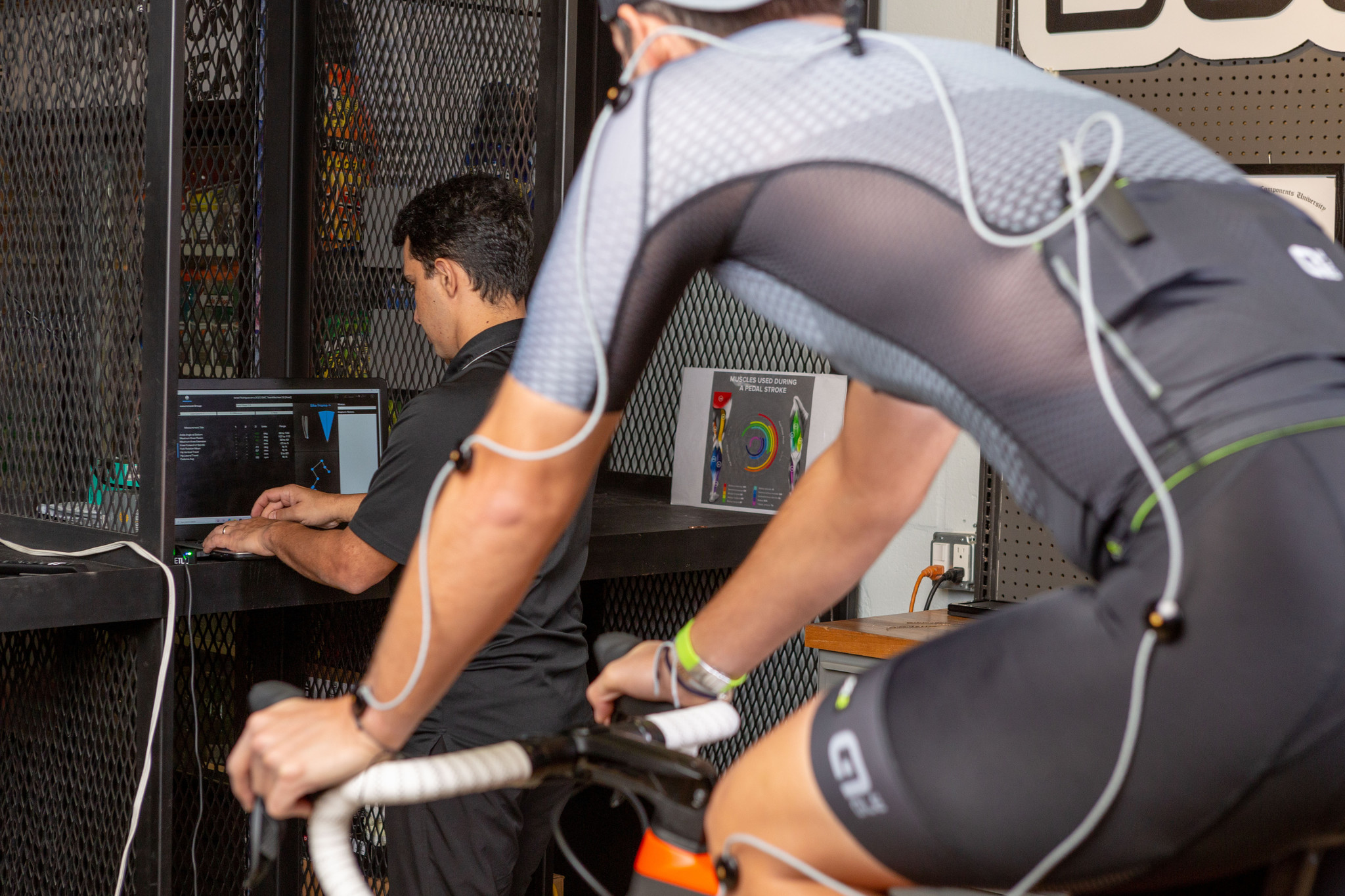 cyclist watching  a man in front of a laptop
