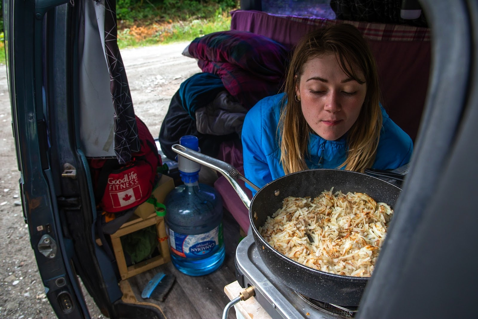 woman cooking dinner at the back of her van