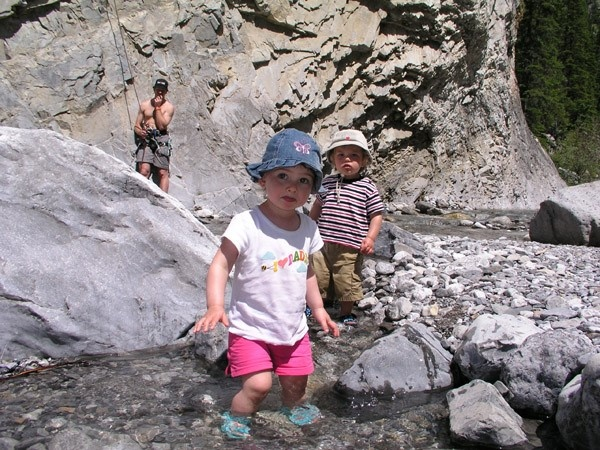 Toddlers playing in the creek with adults climbing in the back