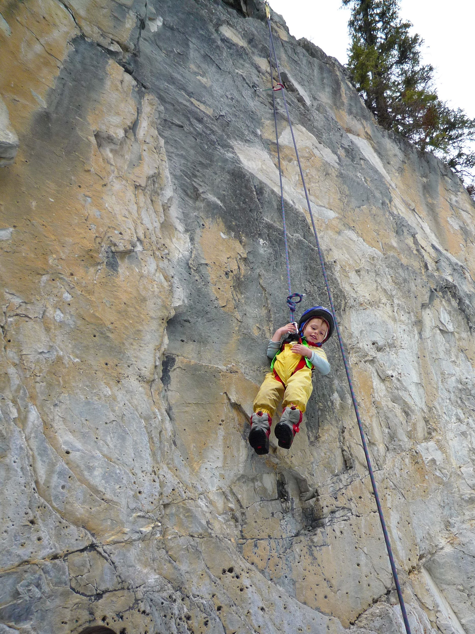 a kid swining on a climbing rope