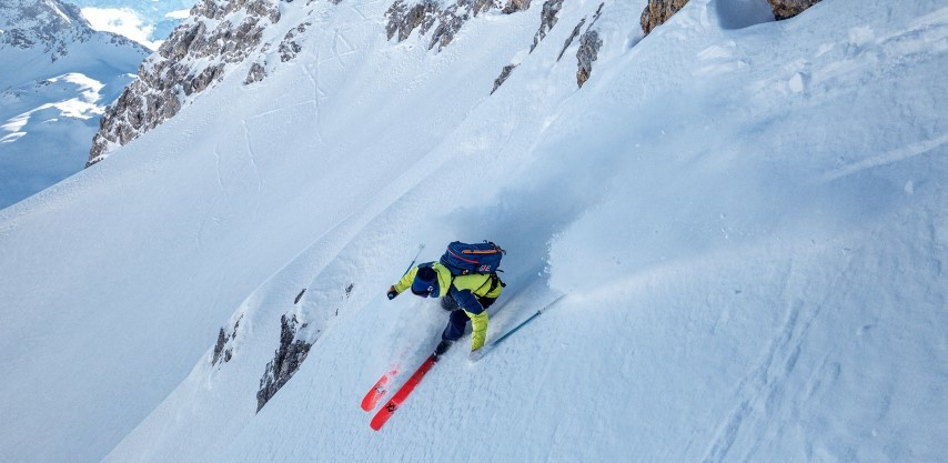 Skier on steep powdery slope skiing the Volkl Rise Beyond 98