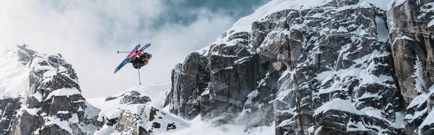Skieur en grab dans les airs, en bas d'une parois