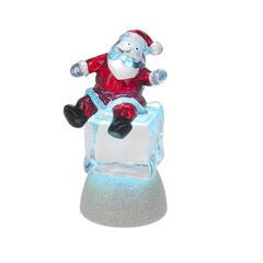 Père Noël sur cube de glace illuminé