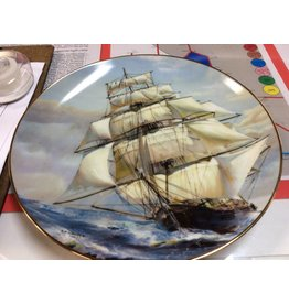 Decor plate ship with lots of sails on ocean