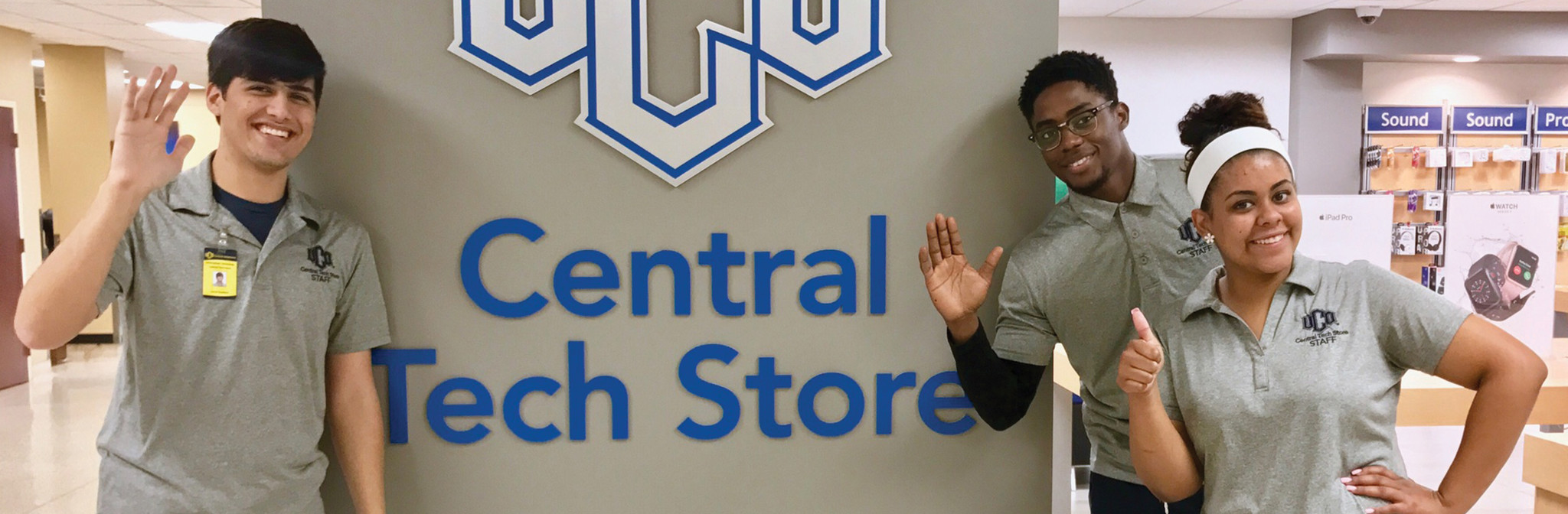 Smiling staff members in front of UCO Central Tech Store sign