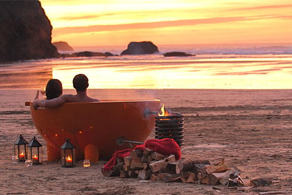 Couple in dutchtub on beach at sunset
