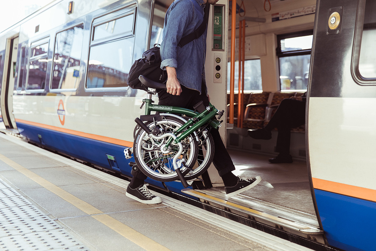 Person boarding a train with a folded bicycle