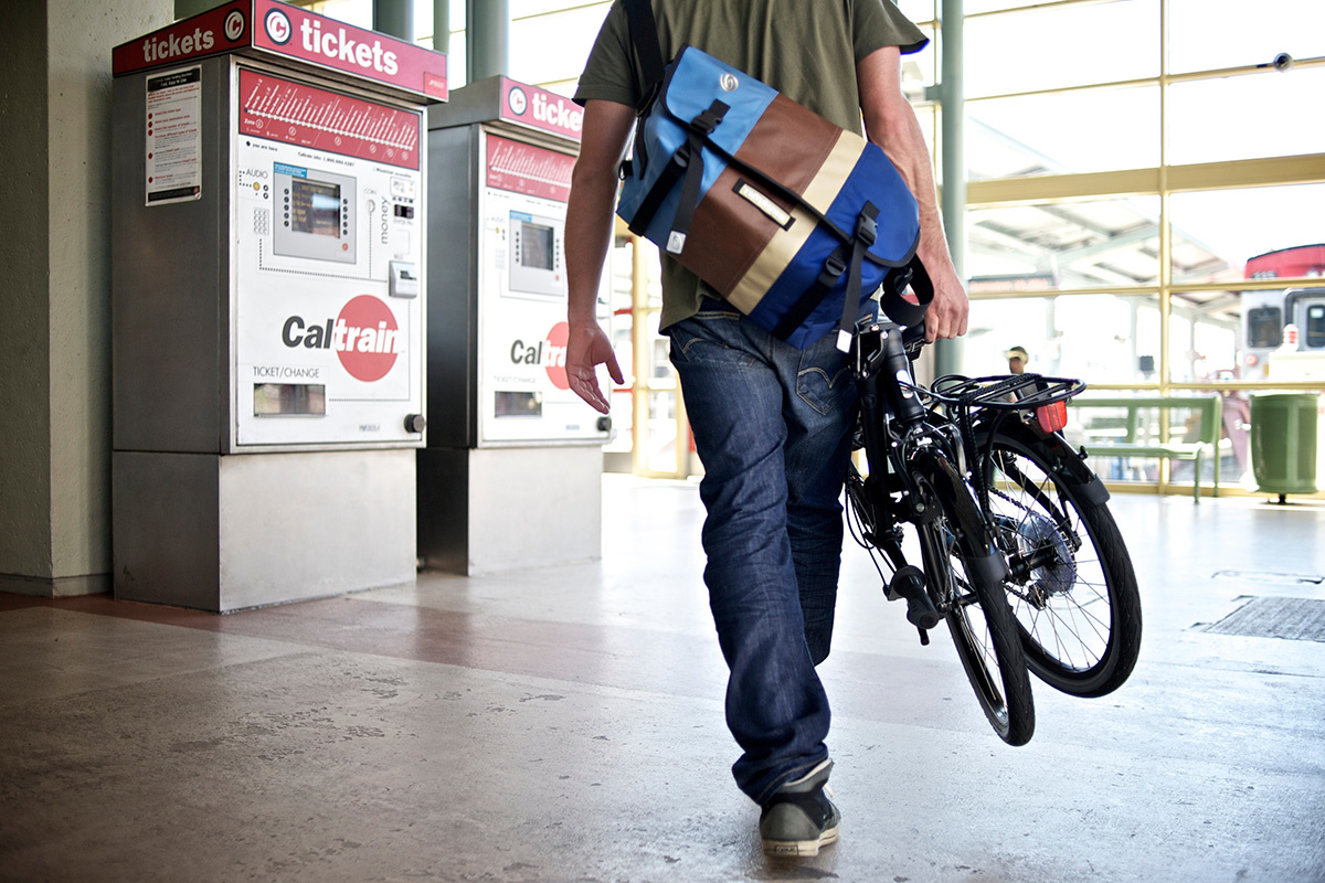 Person carrying a folded bicycle through a train station