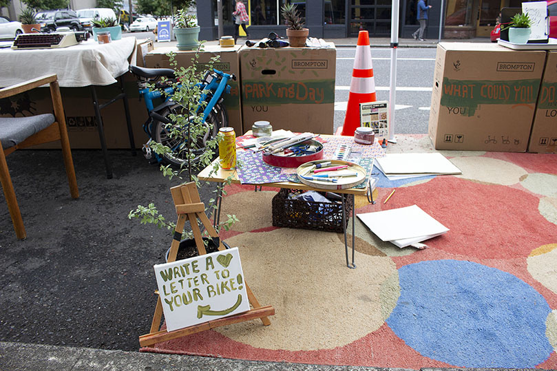 A parking spot outside Clever Cycles with a rug, art supplies, and tables