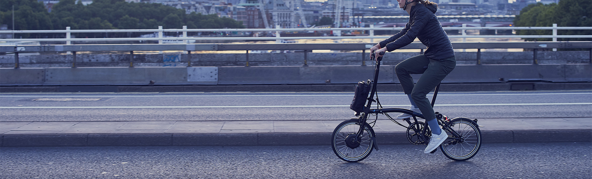 Person riding a Brompton Electric over a bridge with the city skyline in the background