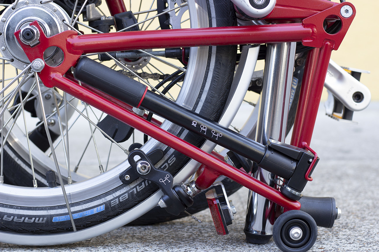 A black hand pump stored in the rear triangle of a folded red Brompton