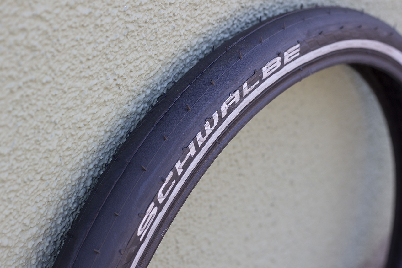 Black, treadless tire with white Schwalbe logo leaning up against a wall
