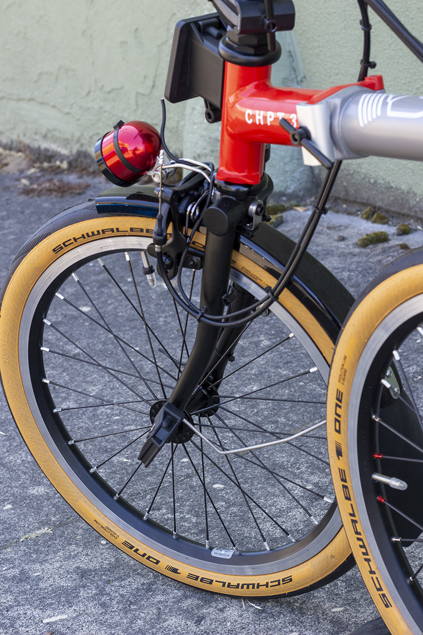 Black tires with tan sidewalls on a Brompton with silver rims, shiny black fenders, a red front light, and a fire red front frame