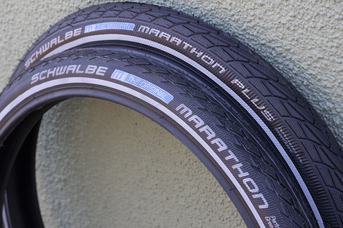 Two black tires, one on top of the other, one with the Schwalbe Marathon logo and one with the Schwalbe Marathon Plus logo