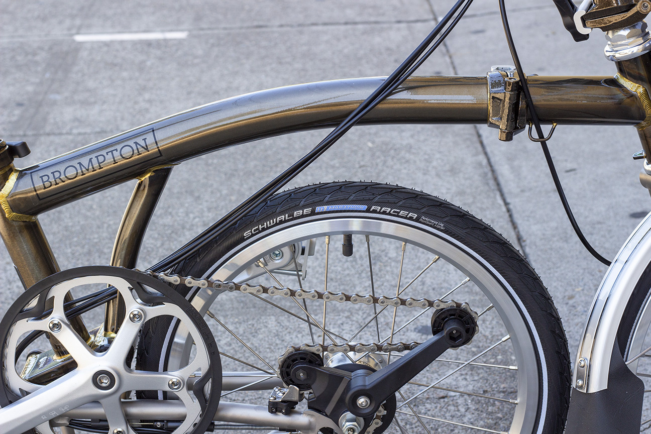 A black tire with a Schwalbe Marathon Racer logo on it on a raw lacquer Brompton in kickstand mode