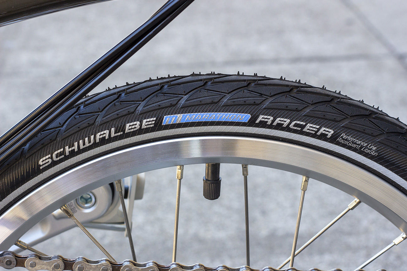 Close-up of a black tire with a light blue and grayish white Schwalbe Marathon Racer logo on the sidewall
