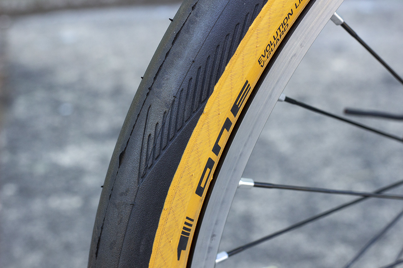 Black tire with light tread, tan sidewall, and Schwalbe One logo on a silver rim with black spokes