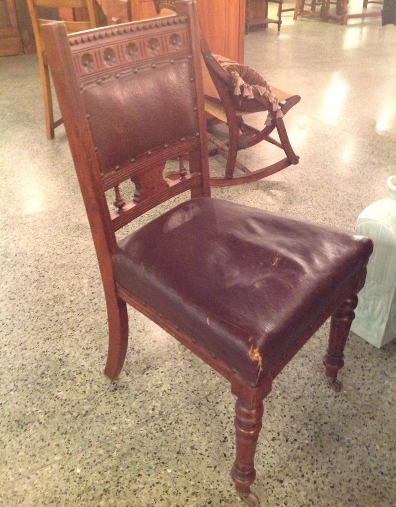 Chair, wooden, rosette design, leather seat and back, wheels on front legs