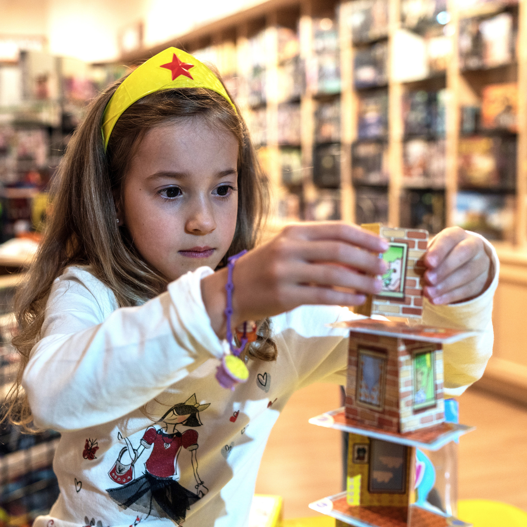 A young girl playing a game of Rhino Hero inside Rain City Games