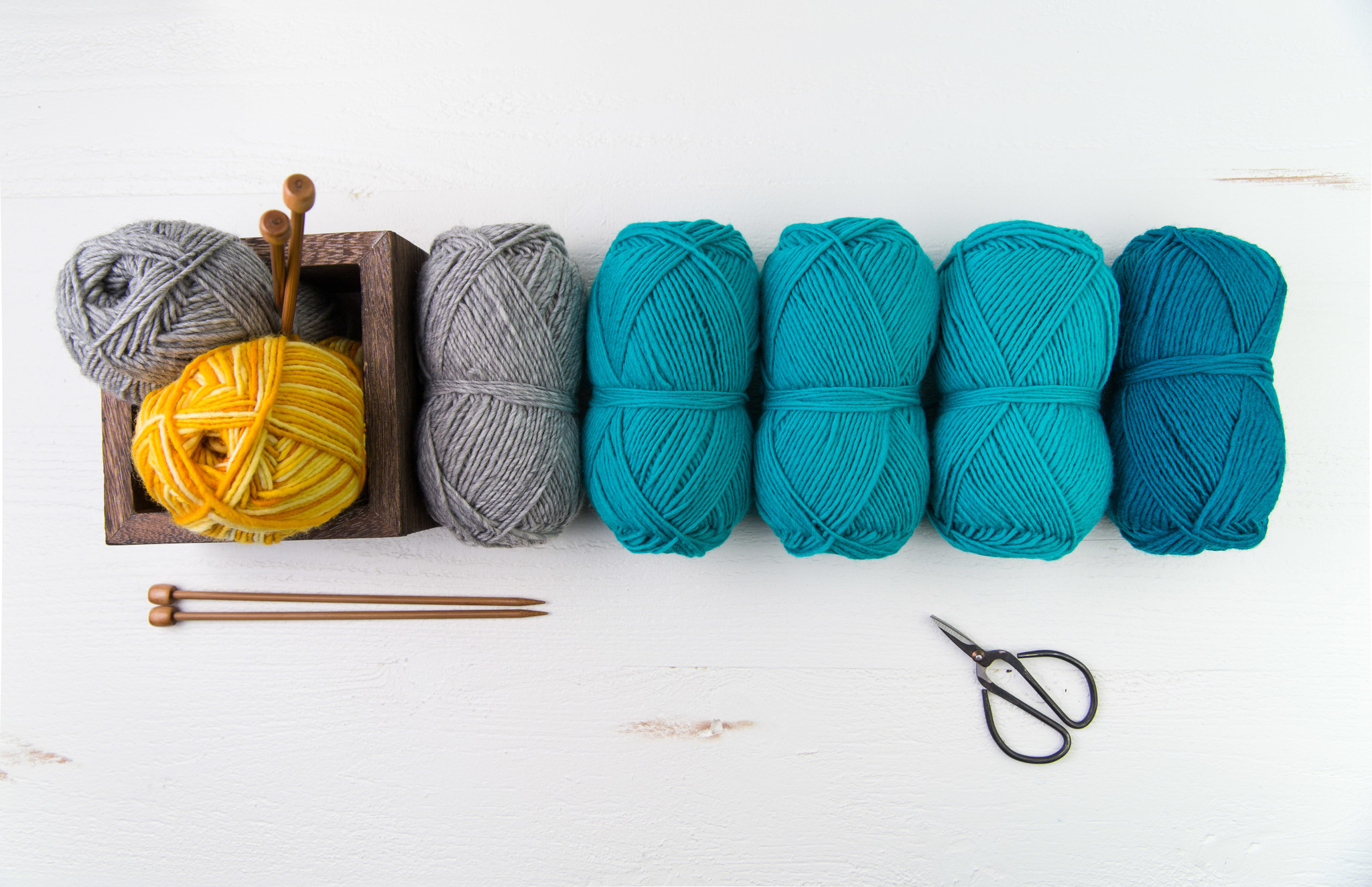 blue and yellow balls of yarn in a row with knitting needles and scissors
