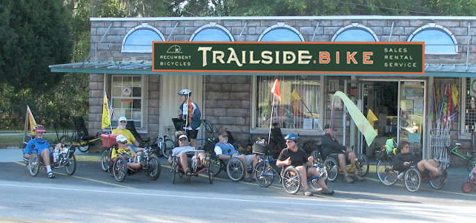 Recumbent trike riders gathered in front of trailside.bike