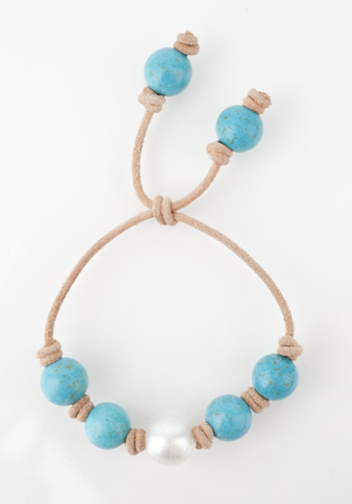 Turquoise with White South Sea Pearl knotted on tan leather cord. Adjustable sliding closure.