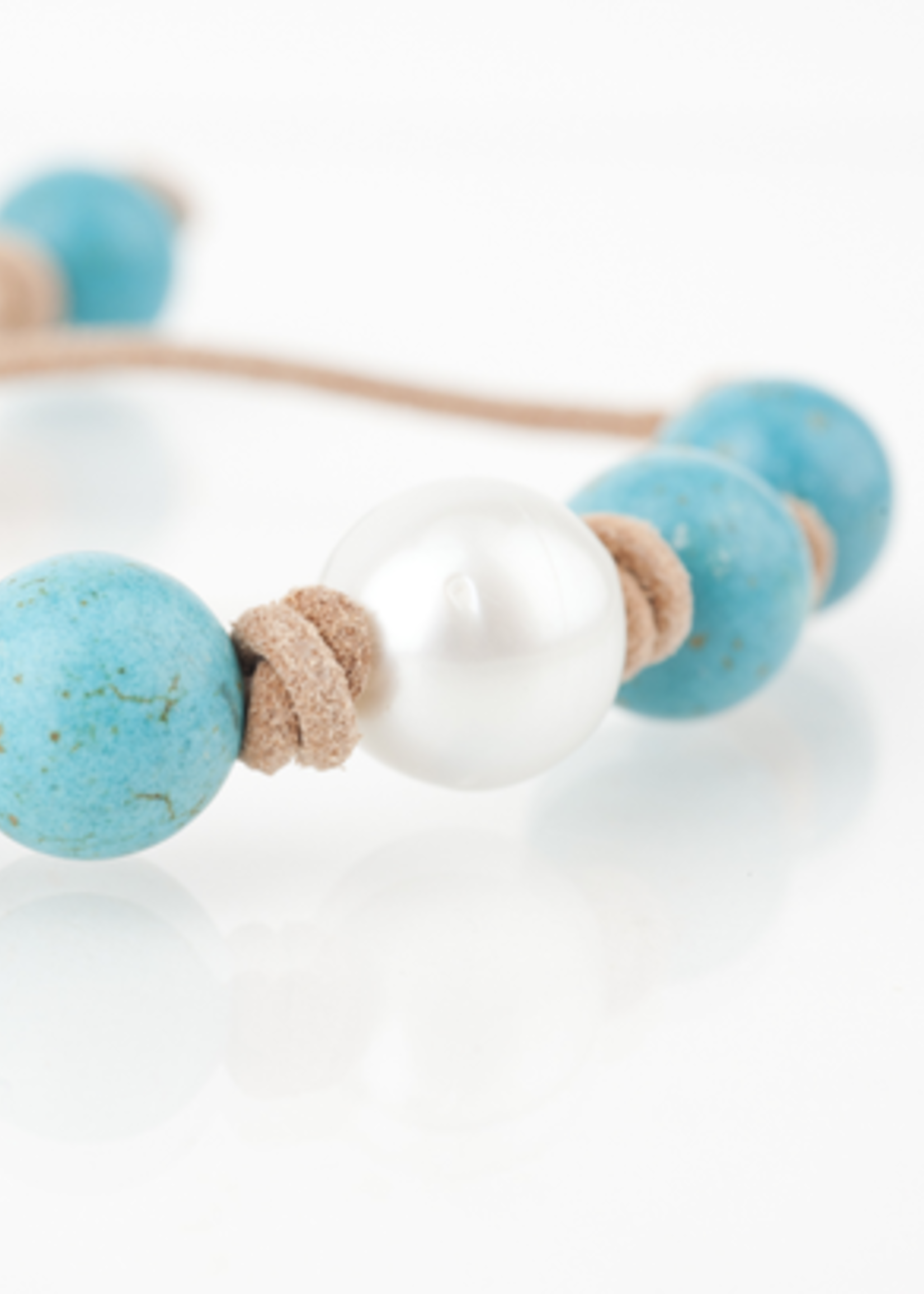 Mina Danielle Turquoise with White South Sea Pearl knotted on tan leather cord. Adjustable sliding closure.