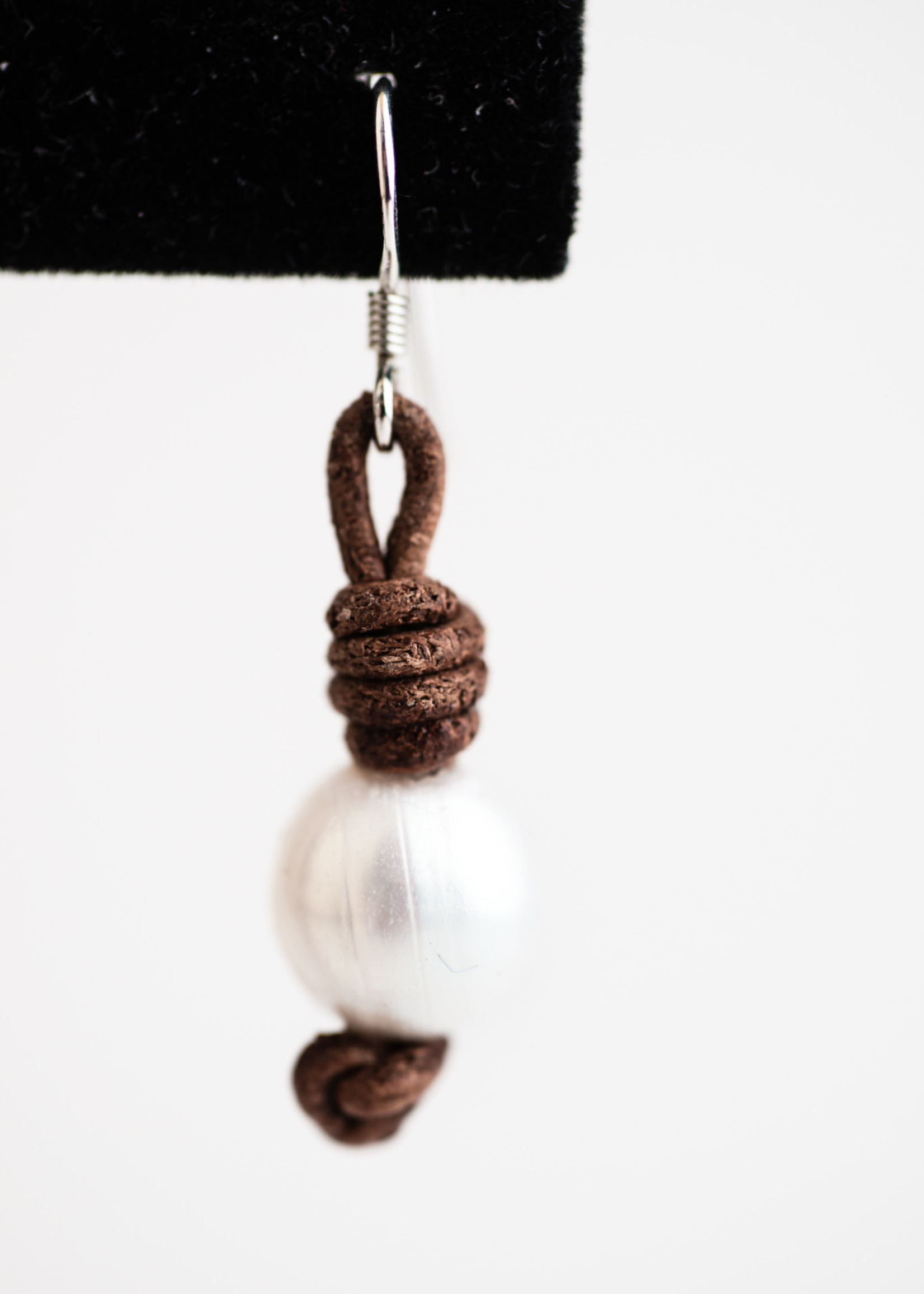 Mina Danielle White Pearl Earrings knotted on Brown Leather