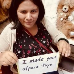 woman with sign that reads 'I made your alpaca toys'